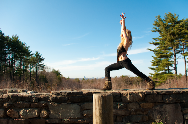 A young woman practices yoga on a wall in a clearing in a pine forest.