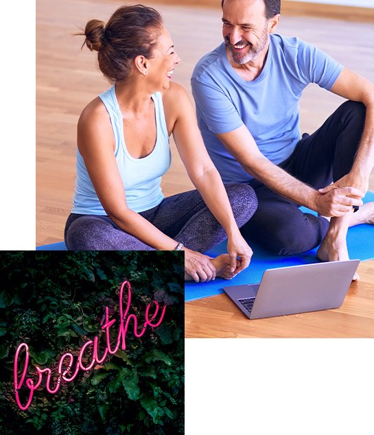 A man and woman sitting on yoga mat in front of a laptop