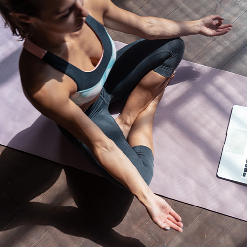 Woman sitting in front of laptop doing Yoga