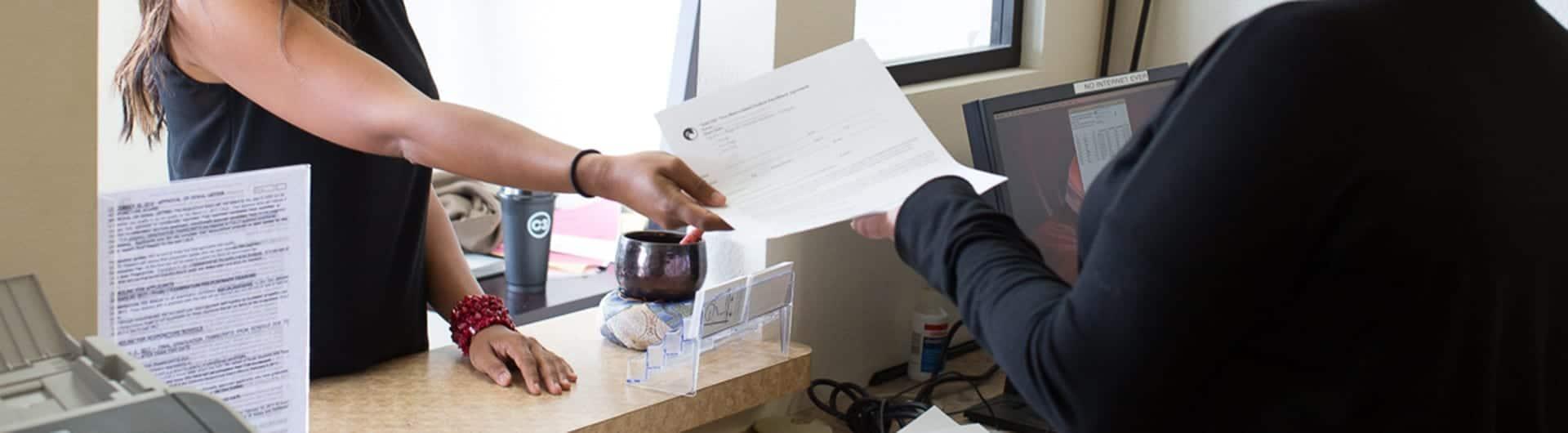 Student handing application to PCOM staff