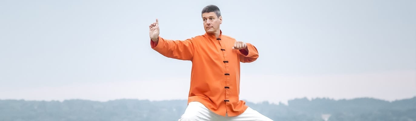 Man doing QiGong by lake