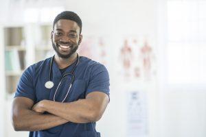 Male nurse standing in scrubs smiling.